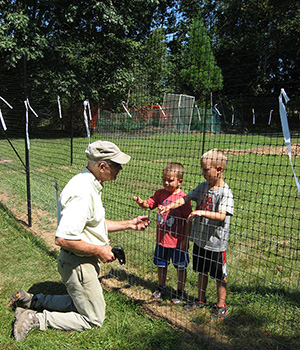 Janis's grandsons, Colbin and Chase, help Ernie attach plastic fencing to wire fencing.