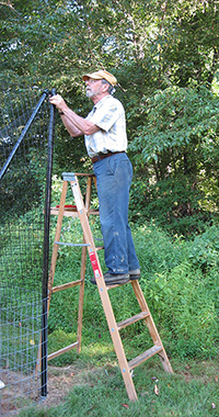 Rick Ray installs plastic fencing above wire fencing.